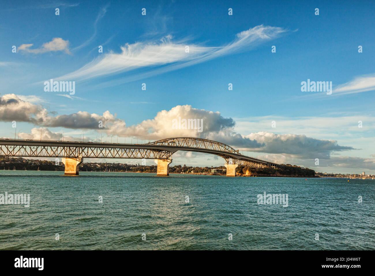 Auckland Harbour Bridge and sunlit clouds. - Stock Image