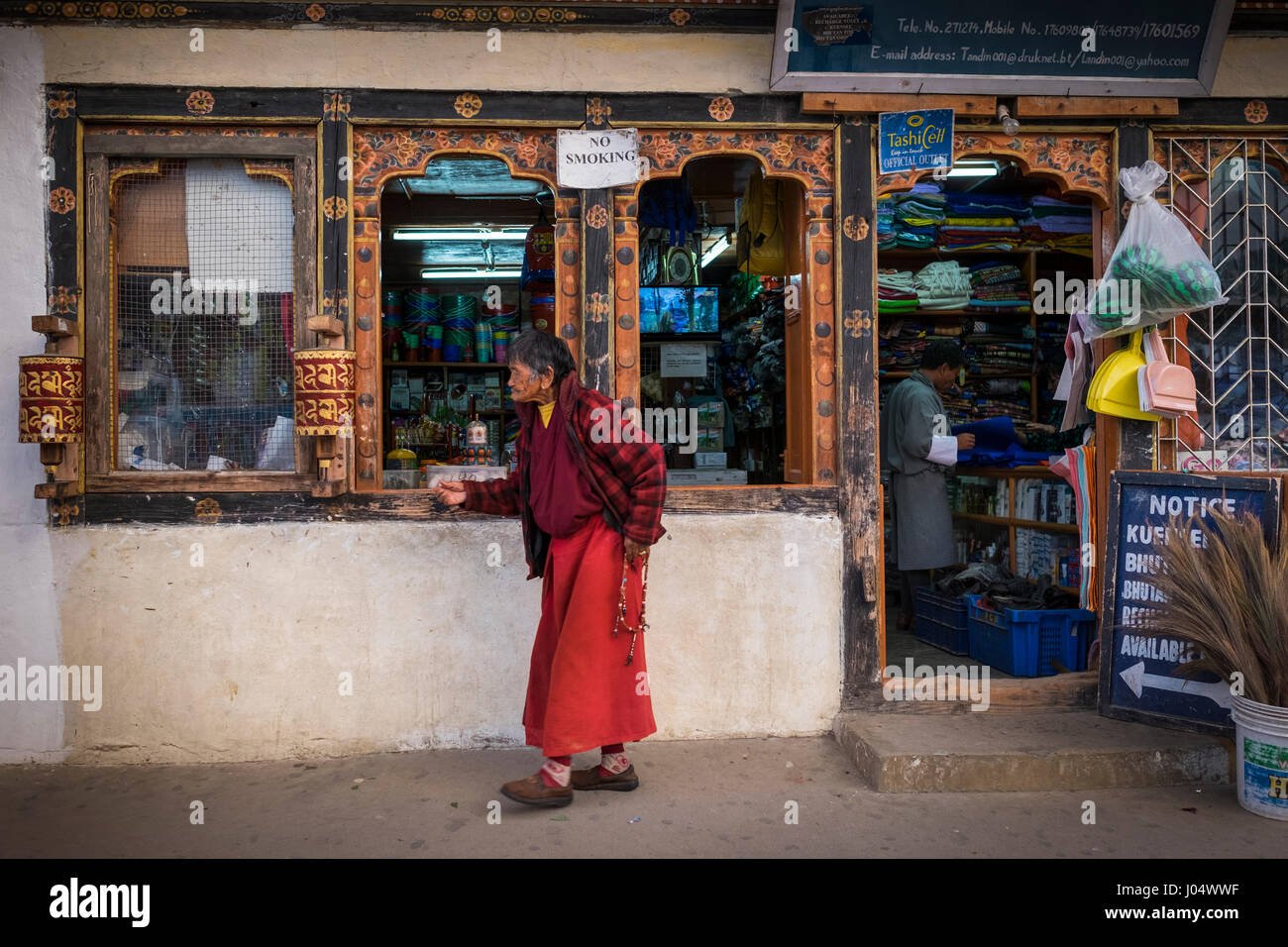 PARO, BHUTAN - CIRCA OCTOBER 2014: Woman walks in front a general store in Paro, Bhutan - Stock Image