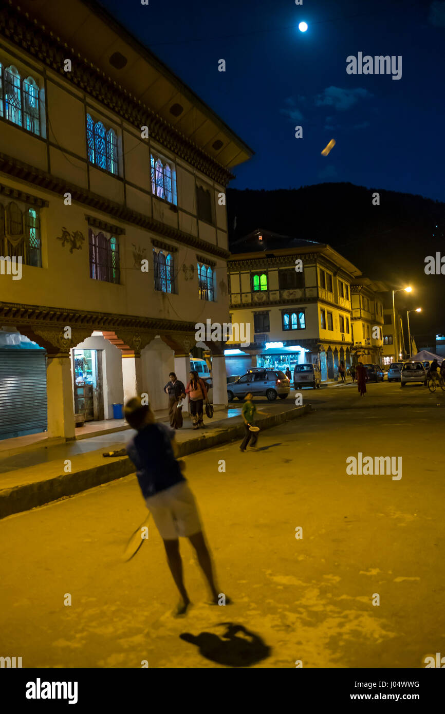PARO, BHUTAN - CIRCA OCTOBER 2014: Kids playing badminton in the streets of Paro at night. - Stock Image
