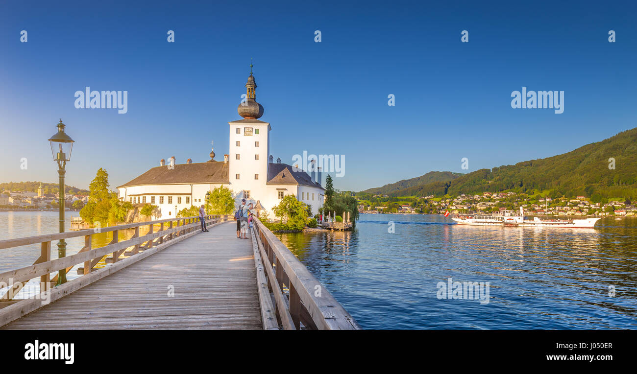Panoramic view of famous Schloss Ort with traditional paddle steamer ship at Lake Traunsee in evening light at sunset, - Stock Image