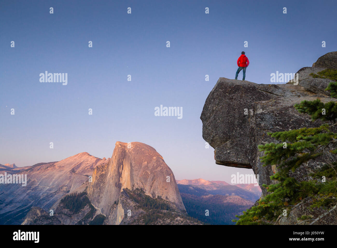 A fearless hiker is standing on an overhanging rock enjoying the view towards famous Half Dome at Glacier Point Stock Photo