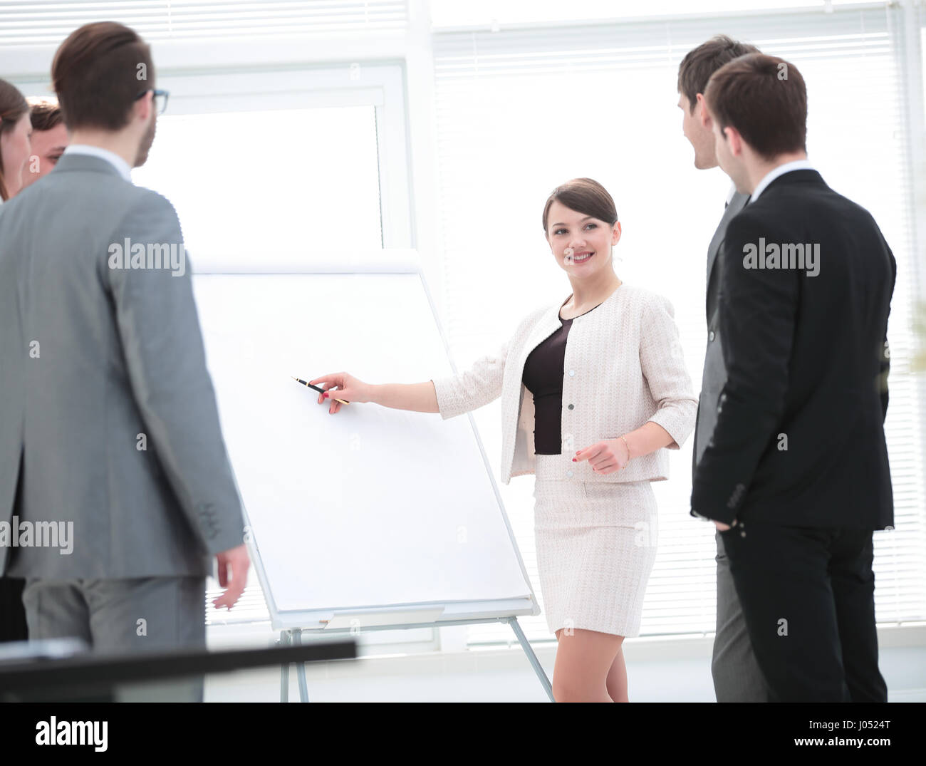 Colleagues asking a question to a businesswoman during a present Stock Photo