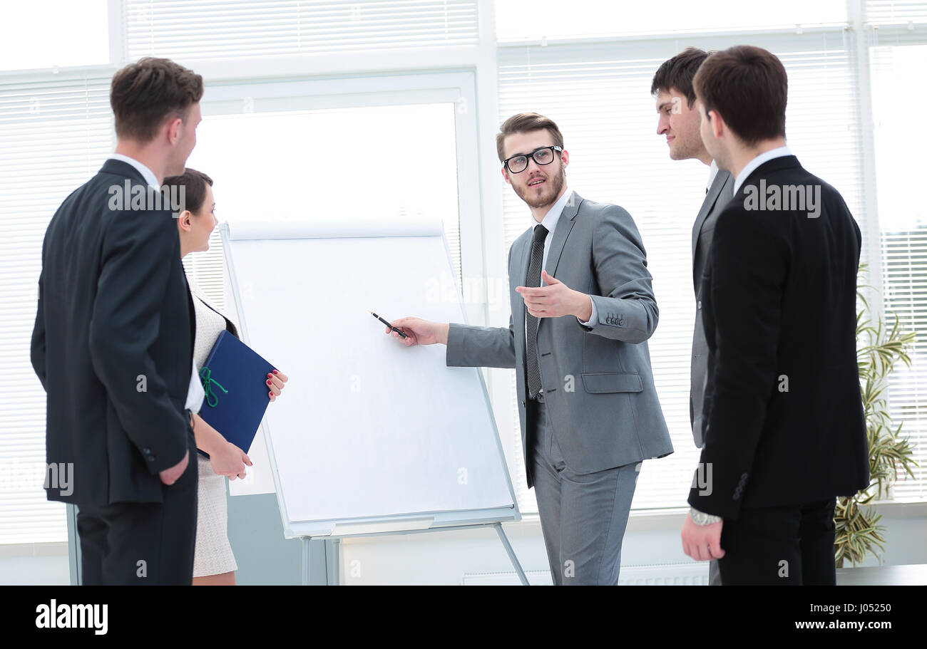 Colleagues asking a question to a businesswoman during a present - Stock Image