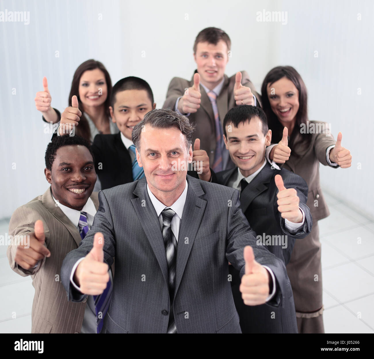 Smiling business people  looking at camera and showing thumbs up - Stock Image