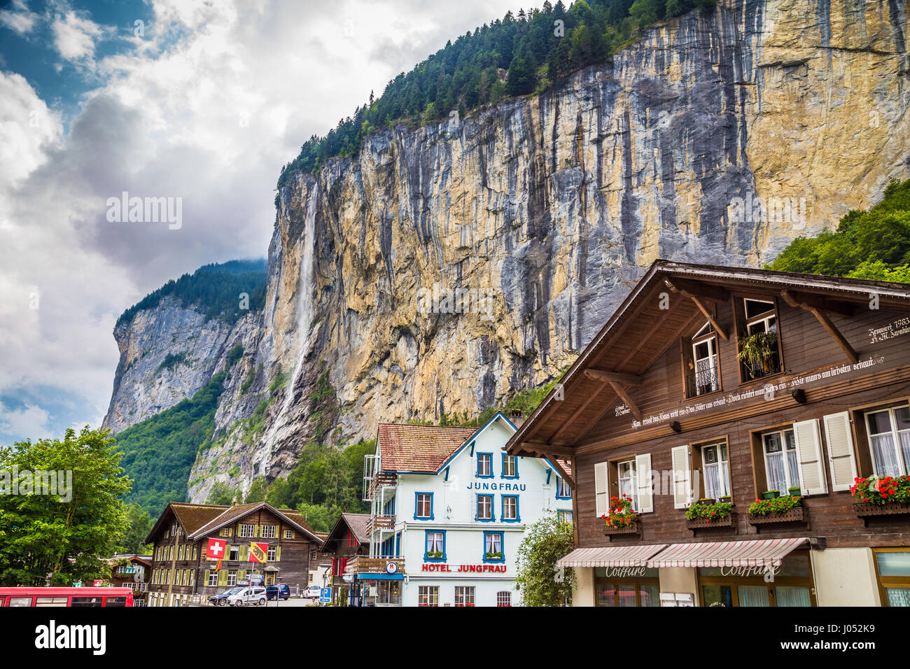 Beautiful view of the historic town of Lauterbrunnen with famous Staubbach Falls in the background on a sunny day - Stock Image