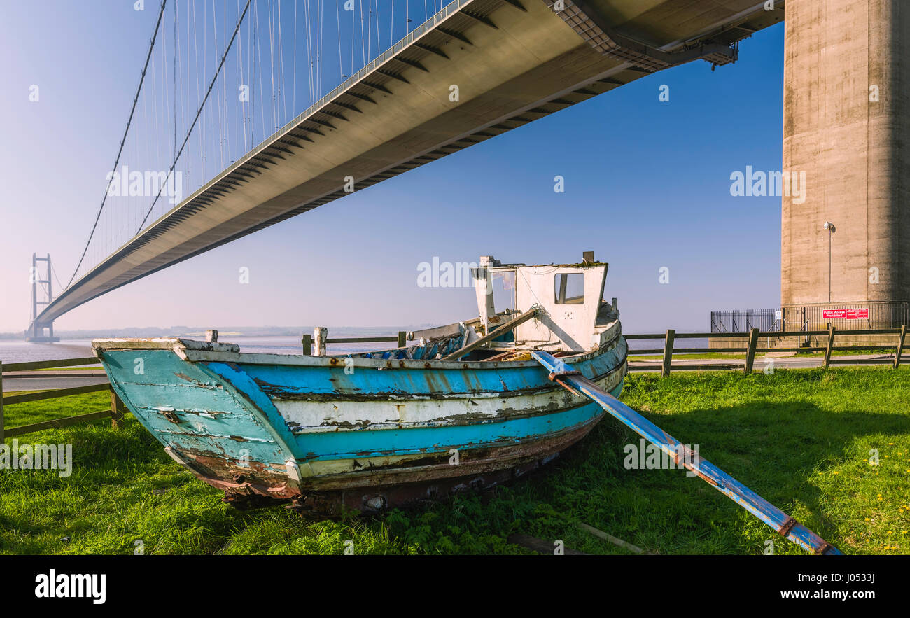 A derelict wooden boat under the Humber Bridge which spans the Humber estuary and viewed on a spring morning in - Stock Image