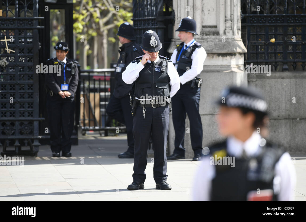 A police officer rubs his eye outside the Houses of Parliament, London, ahead of the funeral of Pc Keith Palmer. - Stock Image