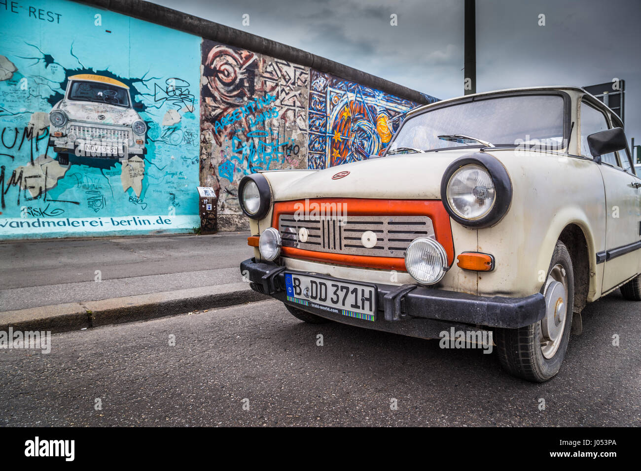 Famous Berliner Mauer (Berlin Wall) at East Side Gallery with an old Trabant, the most common vehicle used in East - Stock Image