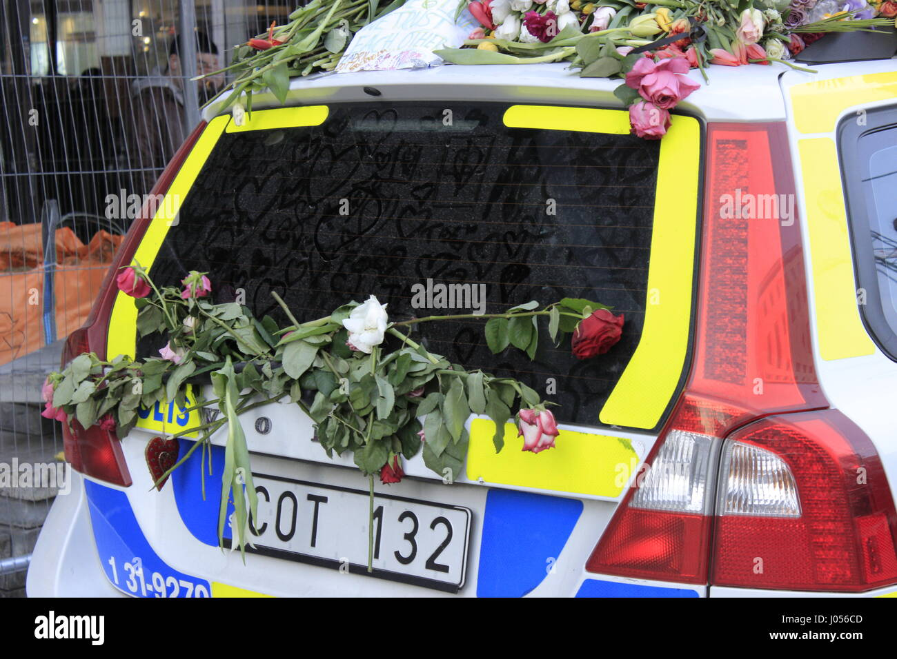 Windshield wiper of a Swedish Police (Polis) car with flowers attached to it and hand-drawn hearts on the windscreen's - Stock Image