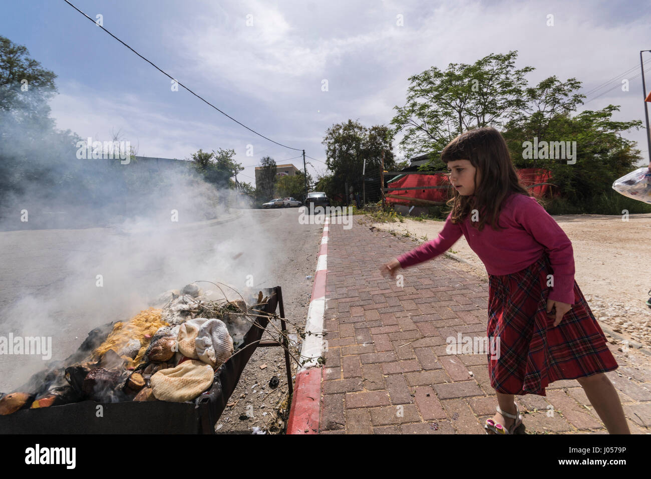 Elkana, Israel. 10th April, 2017. Jewish Orthodox girl burns breads, wheat and flour, as part of the preperations - Stock Image