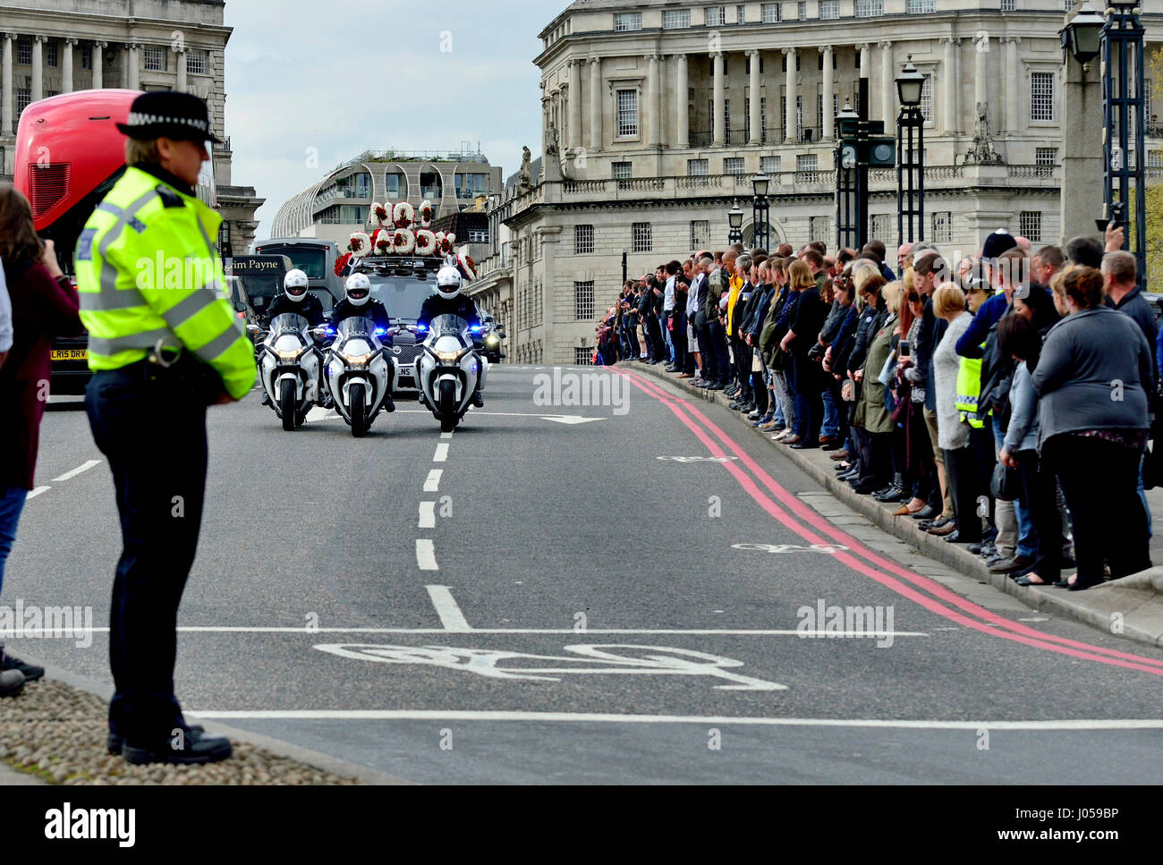 London, UK. 10th Apr, 2017. A police officer bows her head as the funeral cortege of PC Keith Palmer passes over - Stock Image