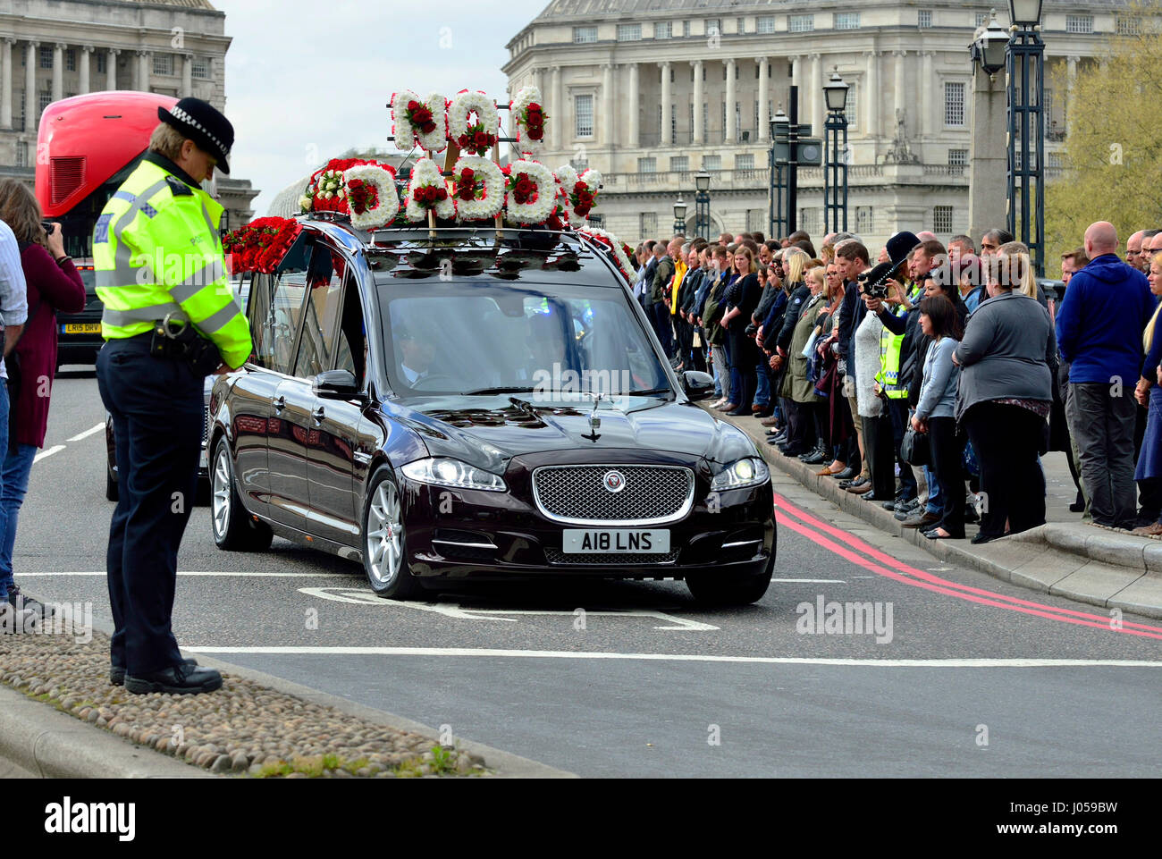 London, UK. 10th Apr, 2017. A police officer bows her head as the funeral cortege of PC Keith Palmer passes over Stock Photo