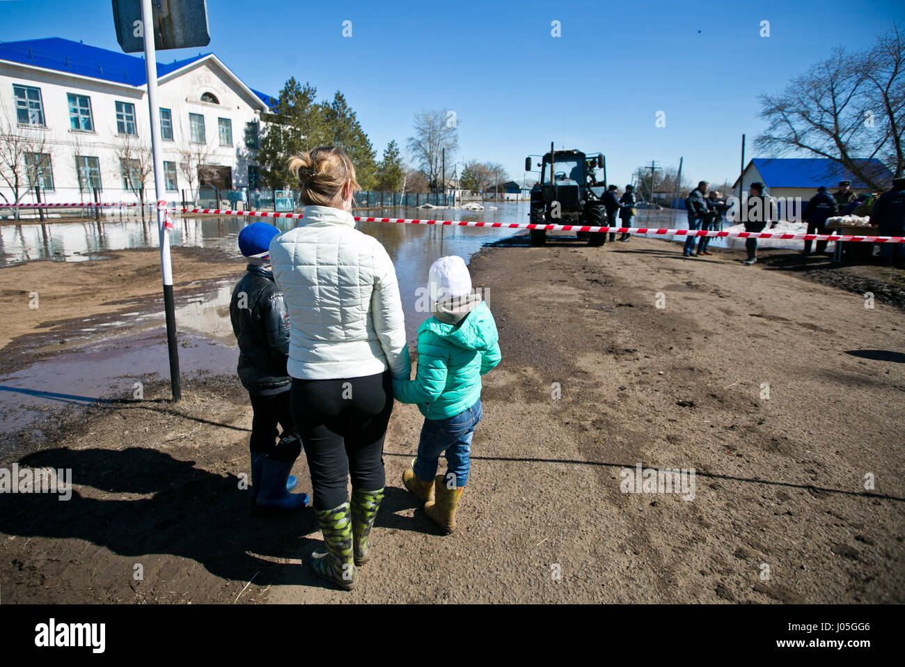 Orenburg Region, Russia. 11th Apr, 2017. Local residents in a street in the village of Krasnokholm flooded due to - Stock Image