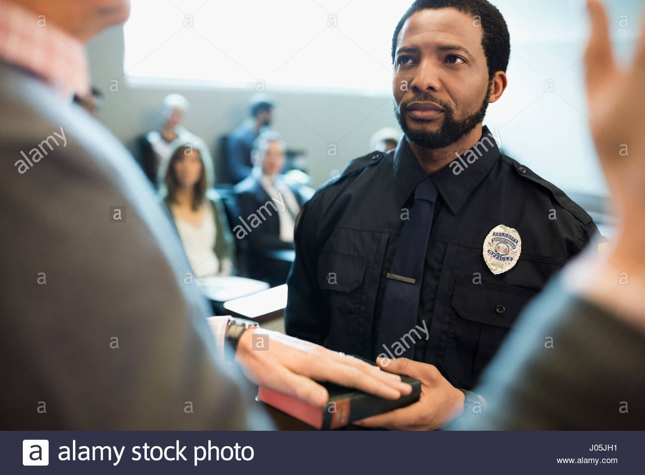 Male bailiff holding bible for witness in legal trial courtroom - Stock Image