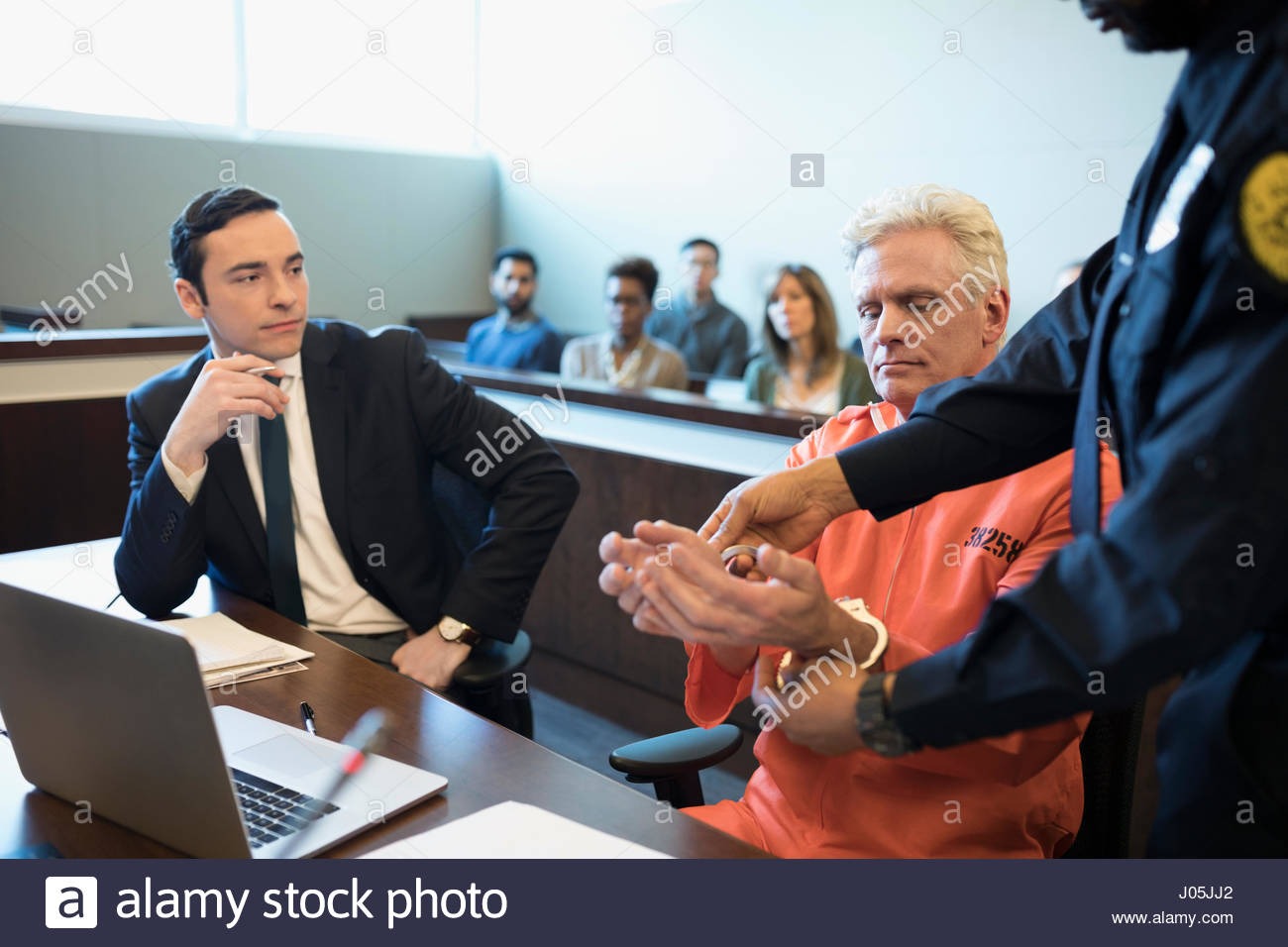 Bailiff handcuffing defendant criminal at table in legal trial courtroom - Stock Image