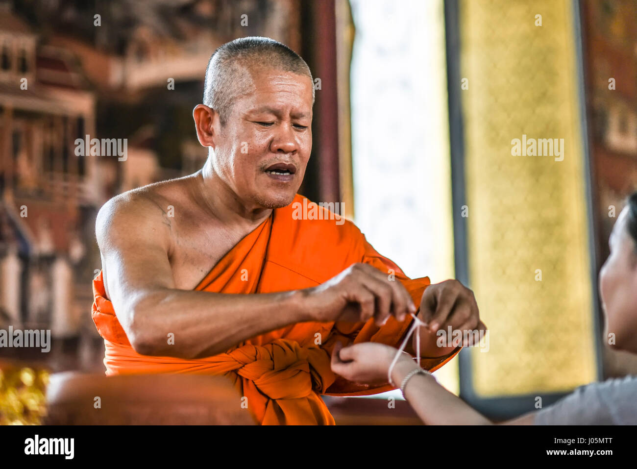 Bangkok, Thailand, March 4, 2016: Monk tieding up a holy thread on a hand in the temple. - Stock Image