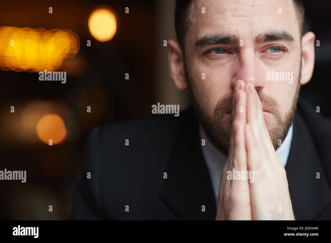 Portrait of modern bearded businessman looking away with red teary eyes, stressed and tired against black background, - Stock Image
