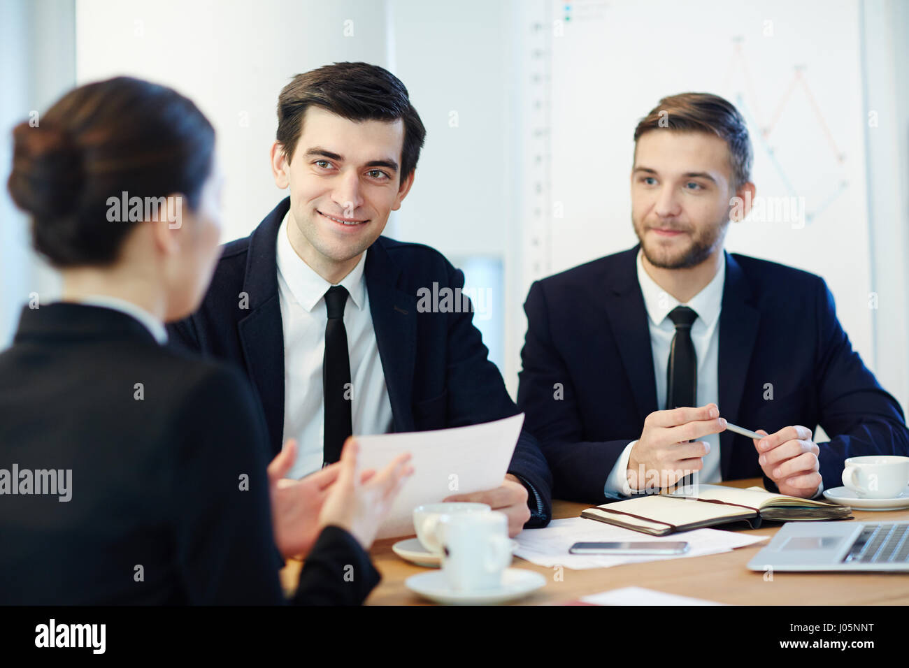 Confident men looking at young co-worker and listening to her - Stock Image
