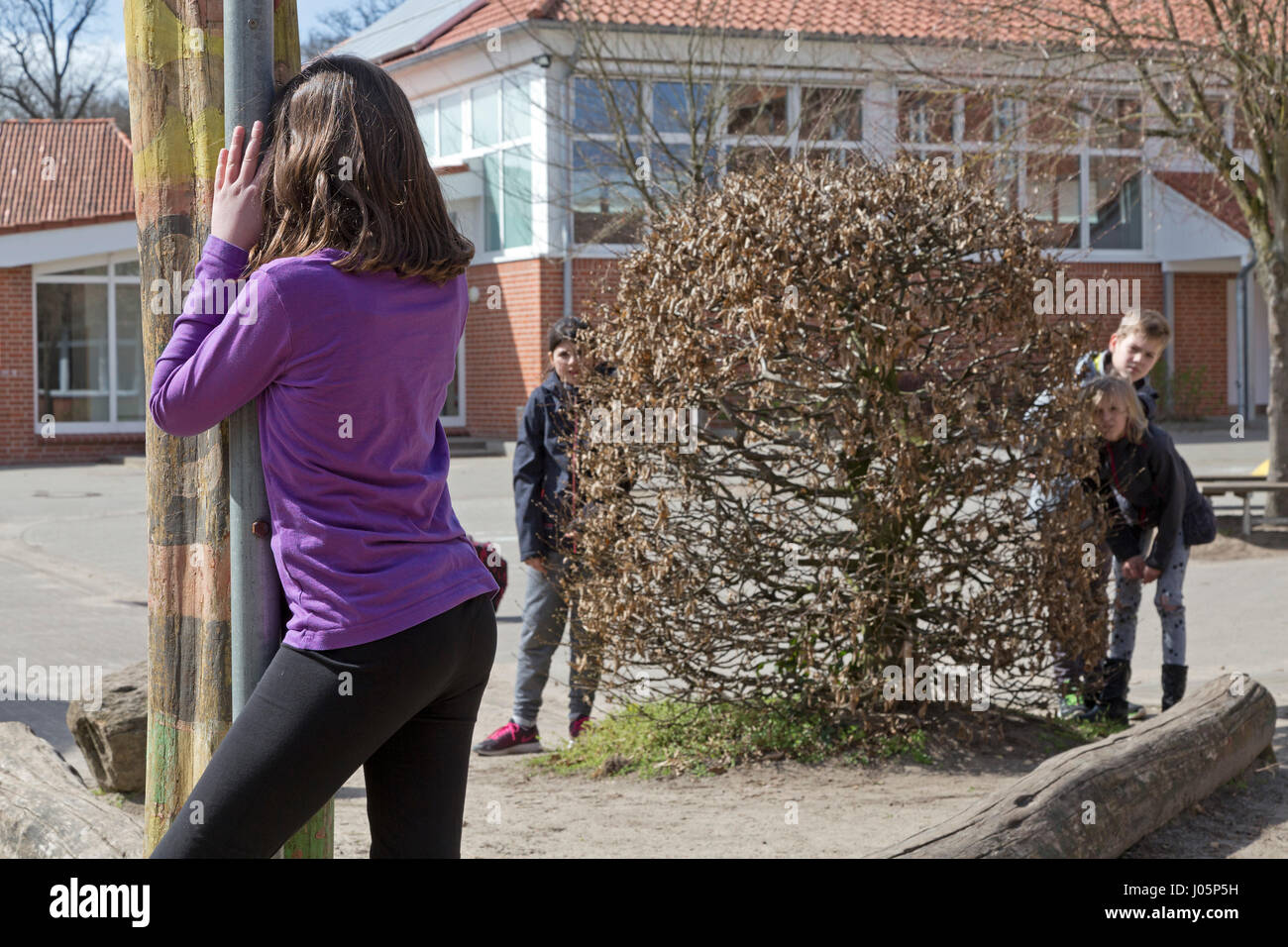 pupils at primary school playing hide and seek during break, Lower Saxony, Germany - Stock Image