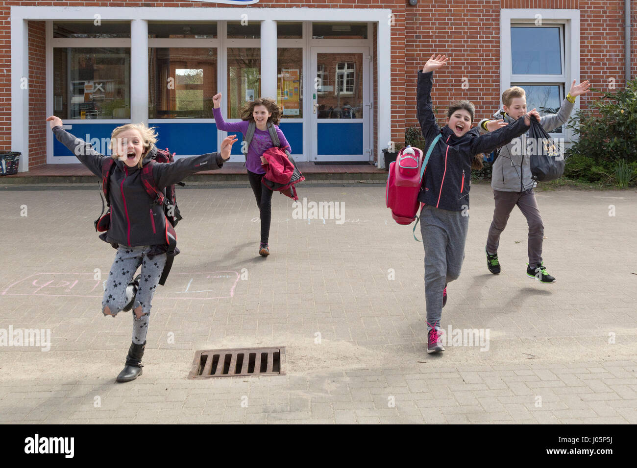 pupils at primary school running into their holidays happily, Lower Saxony, Germany Stock Photo