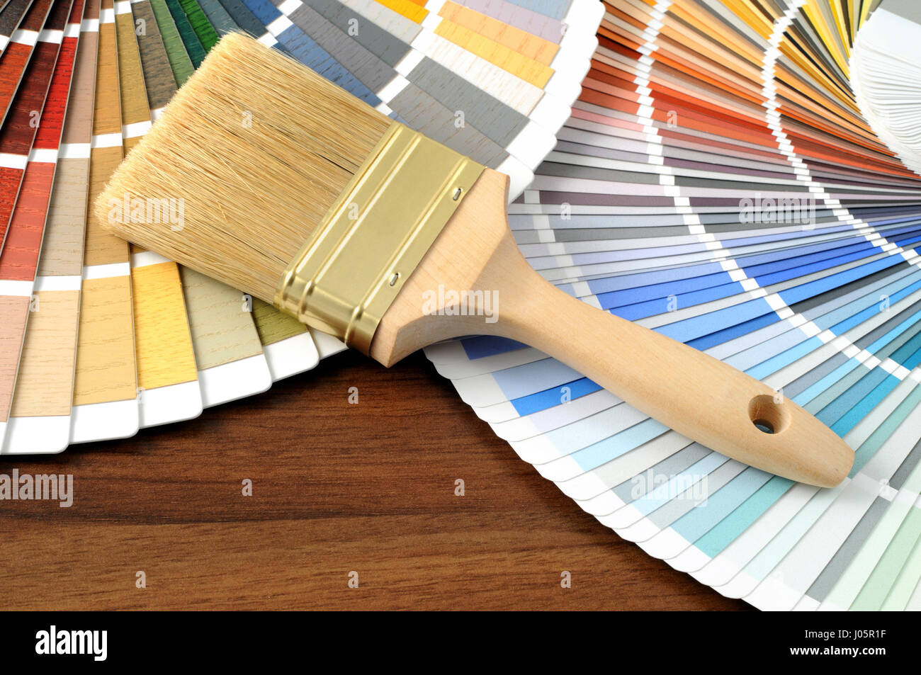 Color swatch on a table with a paintbrush. - Stock Image