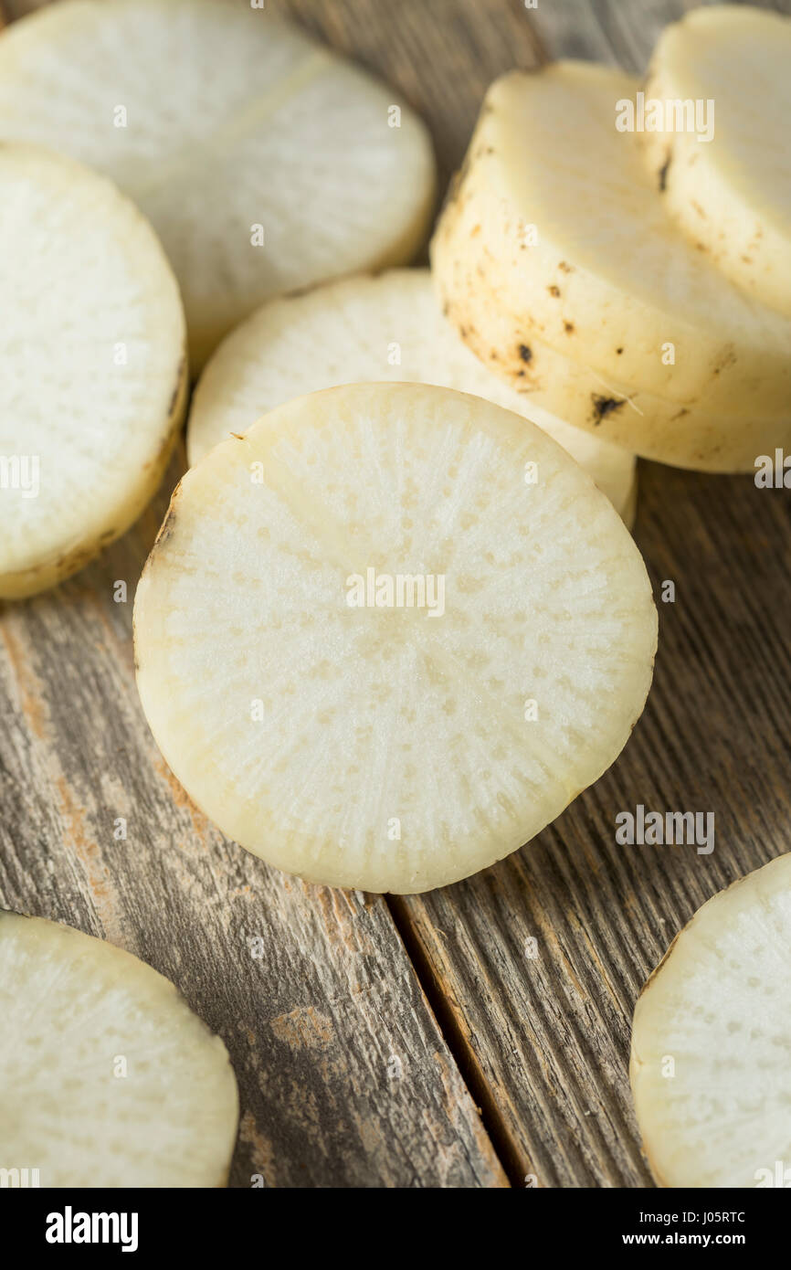 Raw Organic White Daikon with Green Leaves - Stock Image