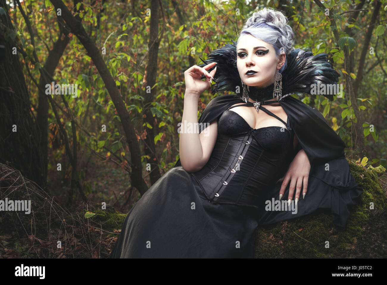 Beautiful young woman a witch, she was in the dark forest. - Stock Image