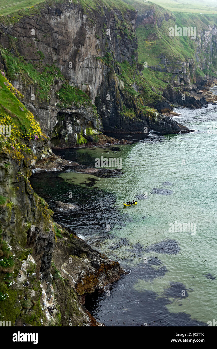 An inflatable canoe below cliffs near the Carrick-a-Rede rope bridge, Causeway Coast, County Antrim, Northern Ireland, - Stock Image