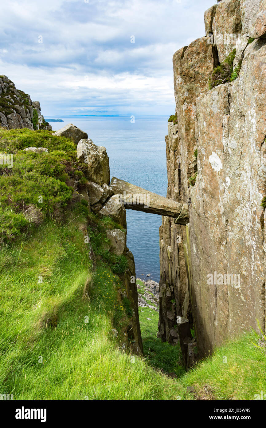 Fallen and wedged rock column, and cliffs near Benmore, or Fair Head, County Antrim, Northern Ireland, UK - Stock Image