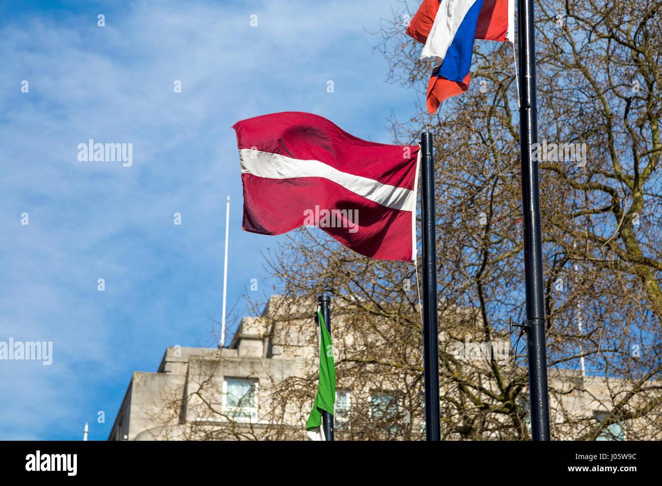 Latvian flag on a flagpole against blue sky - Stock Image
