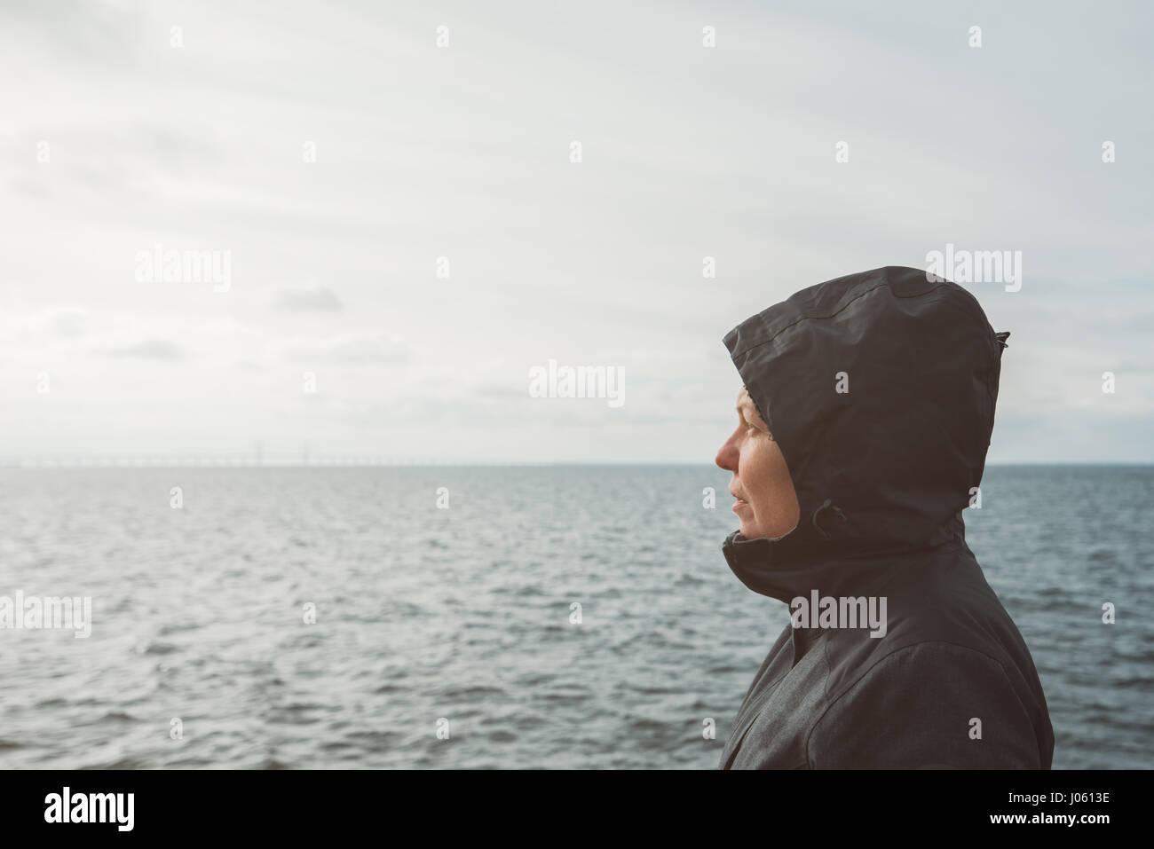 Optimistic female person enjoying morning sunlight at sea coastline on cold windy winter day, anticipating unpredictable - Stock Image