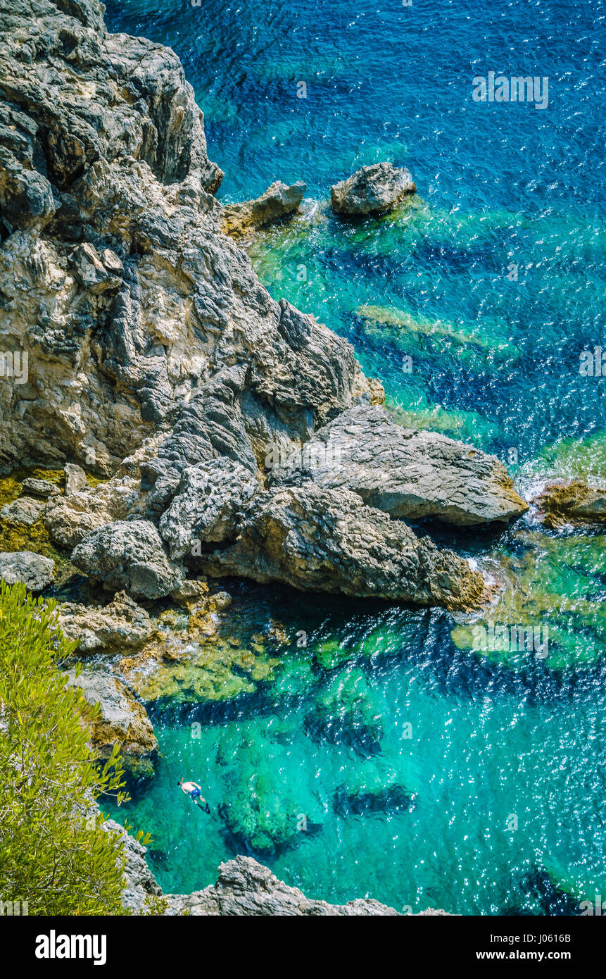 Tourists shorkling between Rocks in Azure Bay of Beautiful Paleokastritsa in Corfu Island, Greece - Stock Image