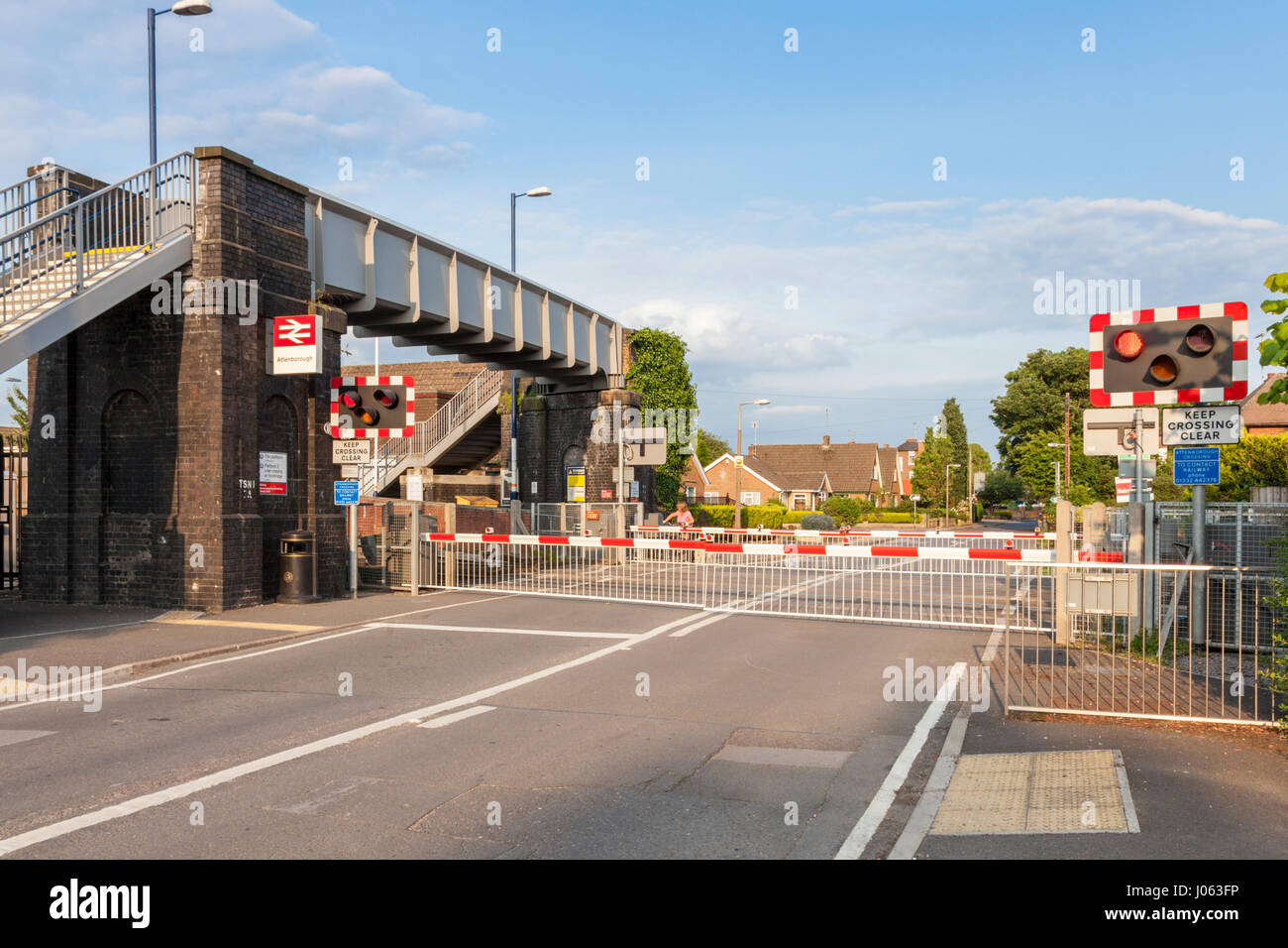 Road with level crossing barriers lowered, Attenborough Railway Station, Nottinghamshire, England, UK - Stock Image