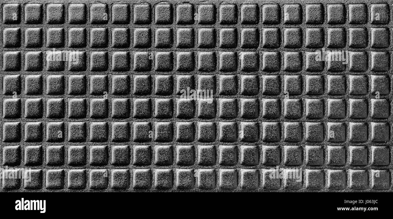Shiny black background, synthetic foamy material with parallel rows. - Stock Image