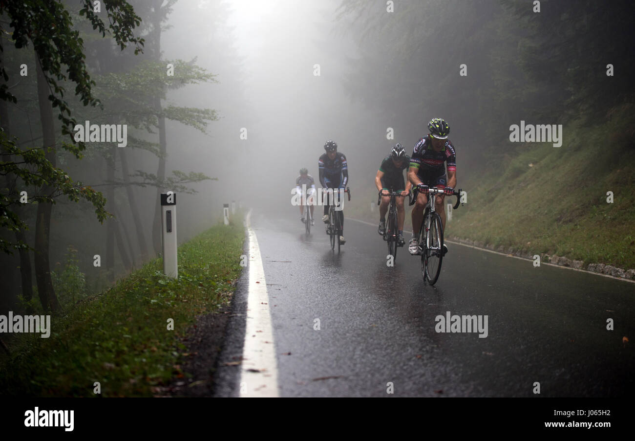 A professional bike rider races up the Geisberg mountain in foggy and rainy weather at the road racing bike race - Stock Image