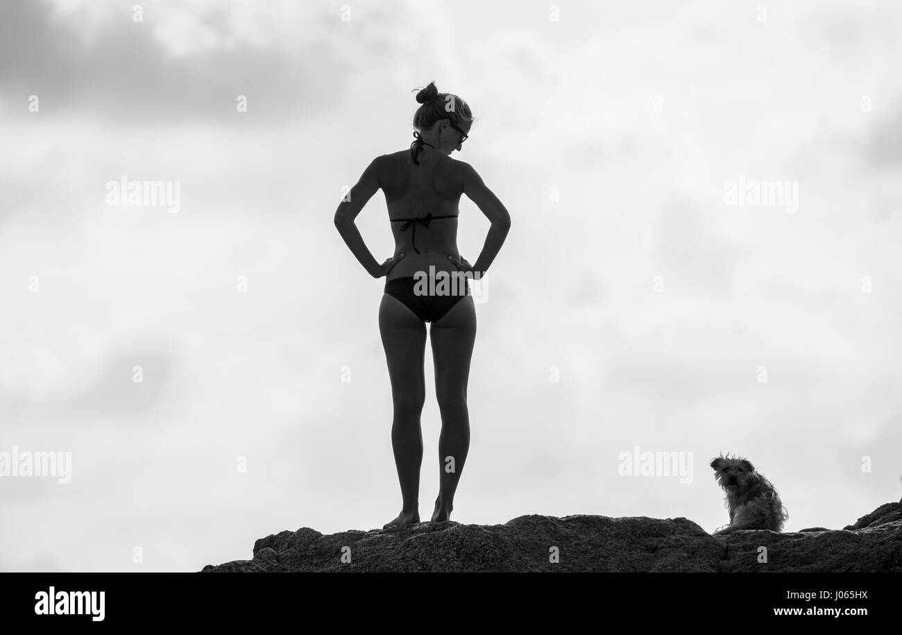 Girl in bikini smiling to her dog in Calvi. Corsica is the most mountainous Mediterranean island and is located - Stock Image