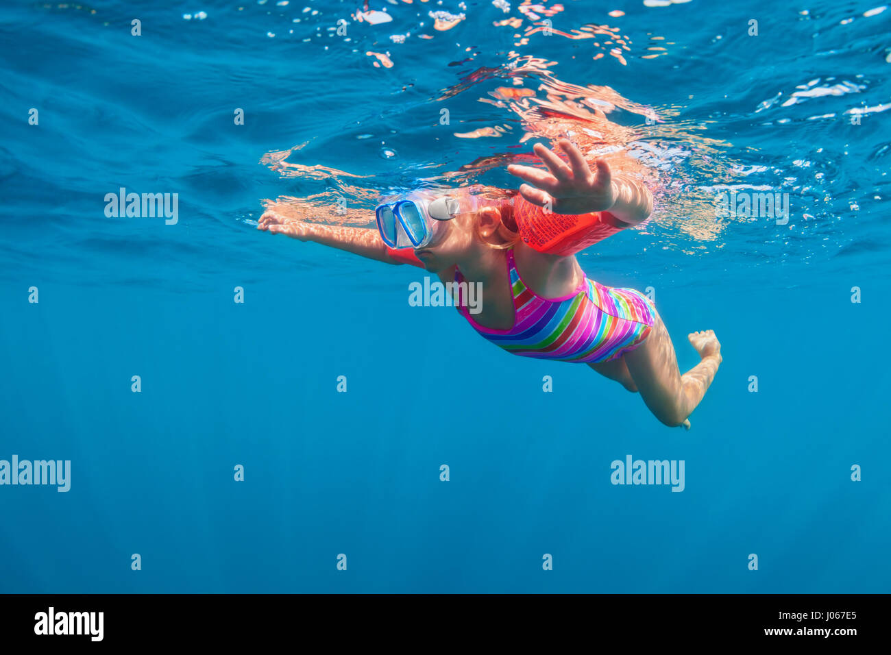 Happy baby girl in snorkeling mask dive underwater with fun in sea pool. Healthy lifestyle, people water sport outdoor - Stock Image