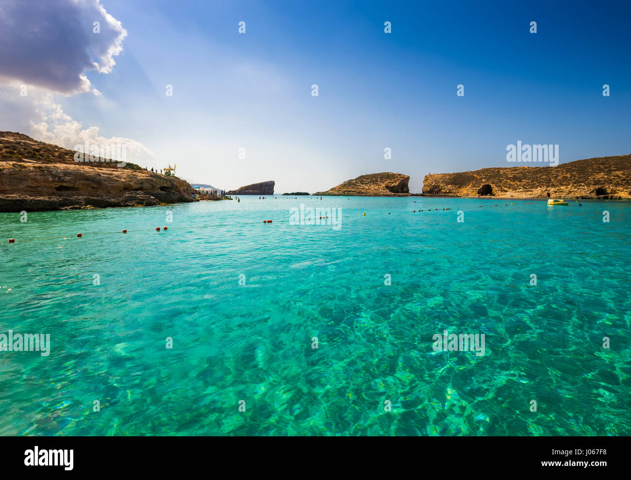 Comino, Malta - The beautiful azure sea water at the Blue Lagoon on the island of Comino on a bright sunny summer - Stock Image