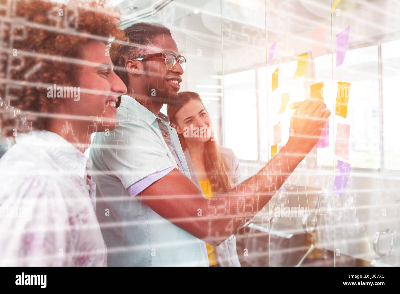 Stocks and shares against creative bussiness people discussing over adhesive notes - Stock Image