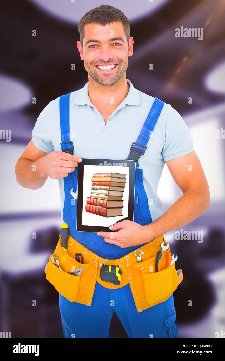 Happy repairman in overalls holding digital tablet against classroom Stock Photo
