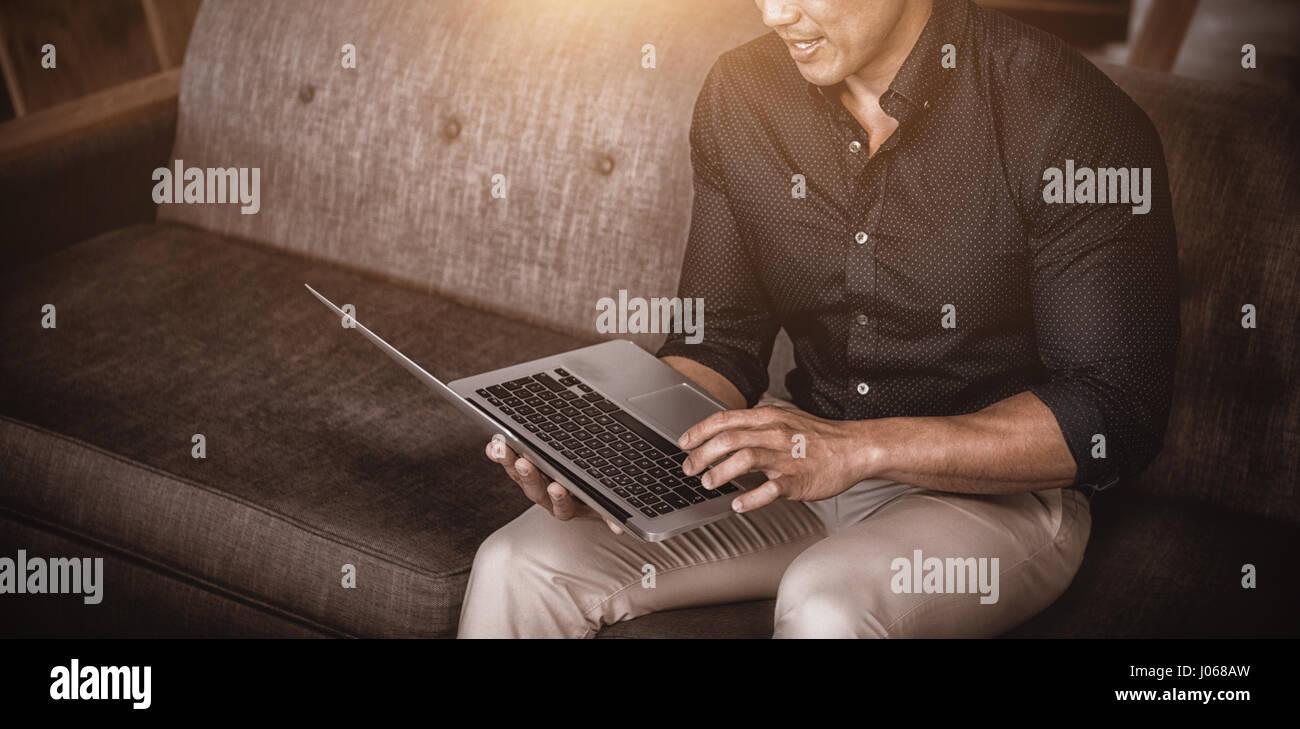 Businessperson sitting on sofa using laptop - Stock Image