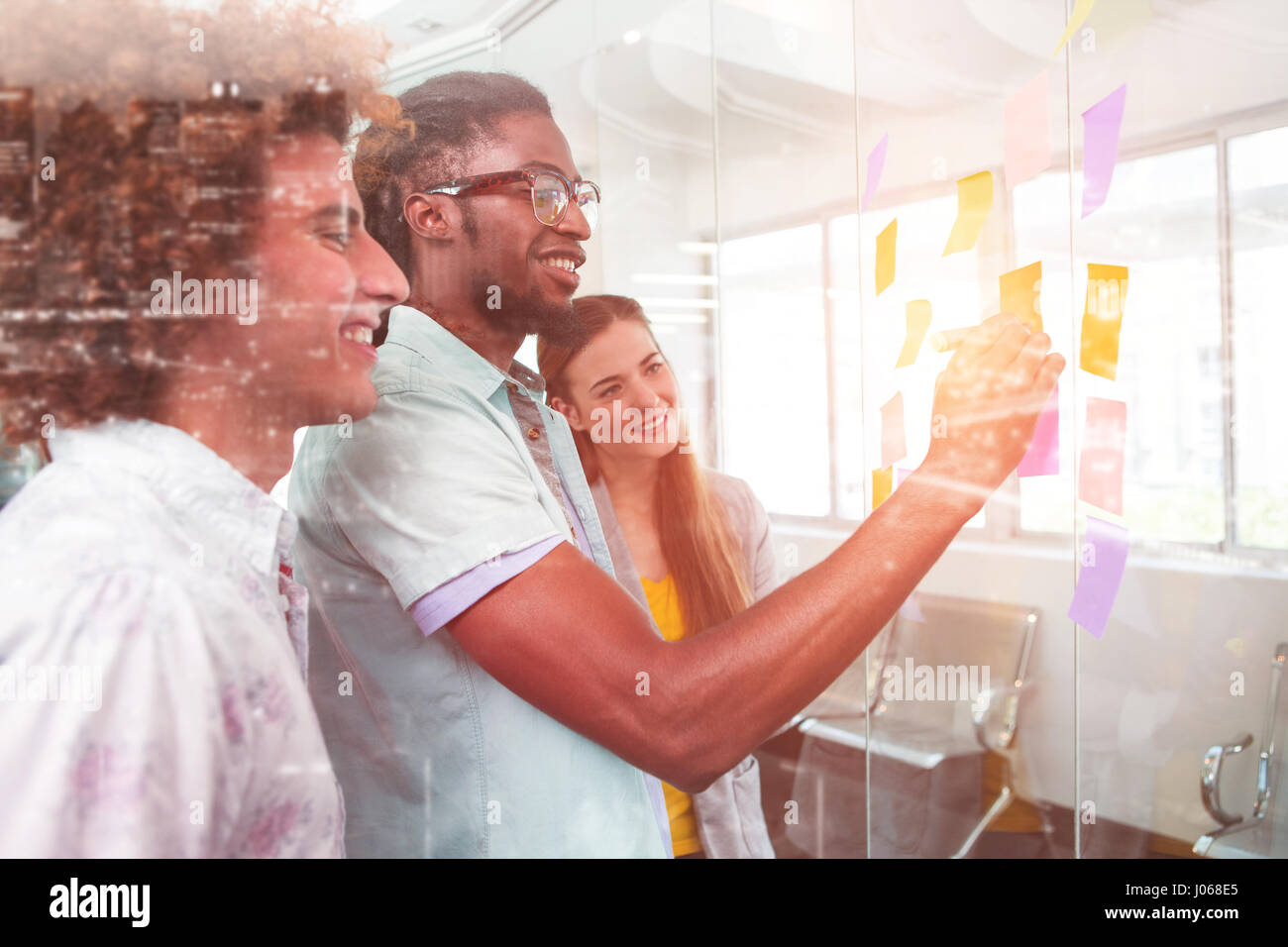 High angle view of illuminated cityscape against creative bussiness people discussing over adhesive notes - Stock Image
