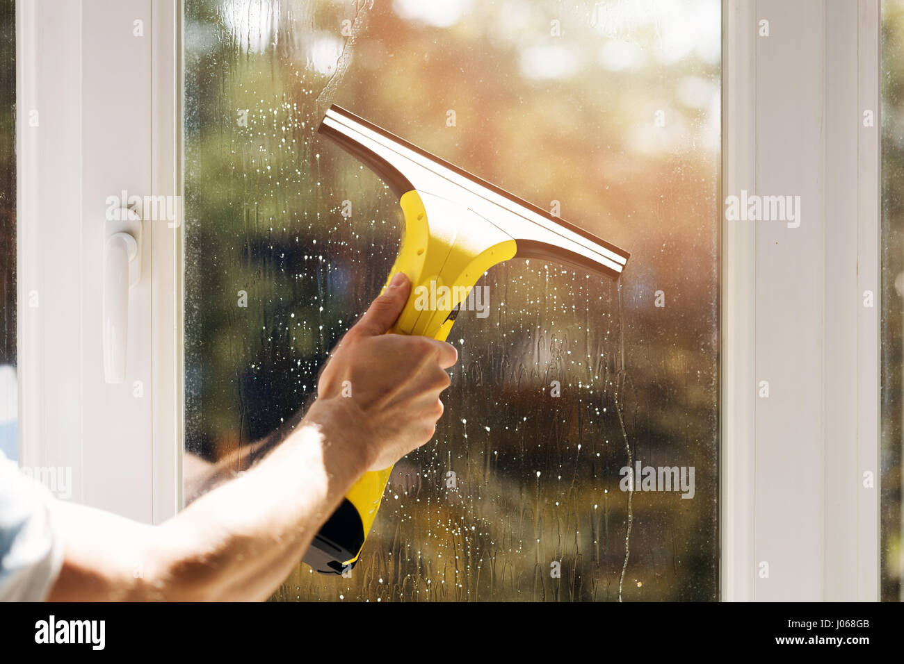 hand cleaning window with vacuum cleaner - Stock Image