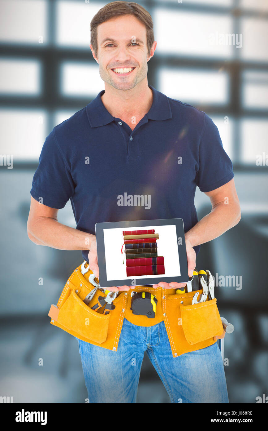 Happy carpenter holding digital tablet against chairs arranged by table Stock Photo