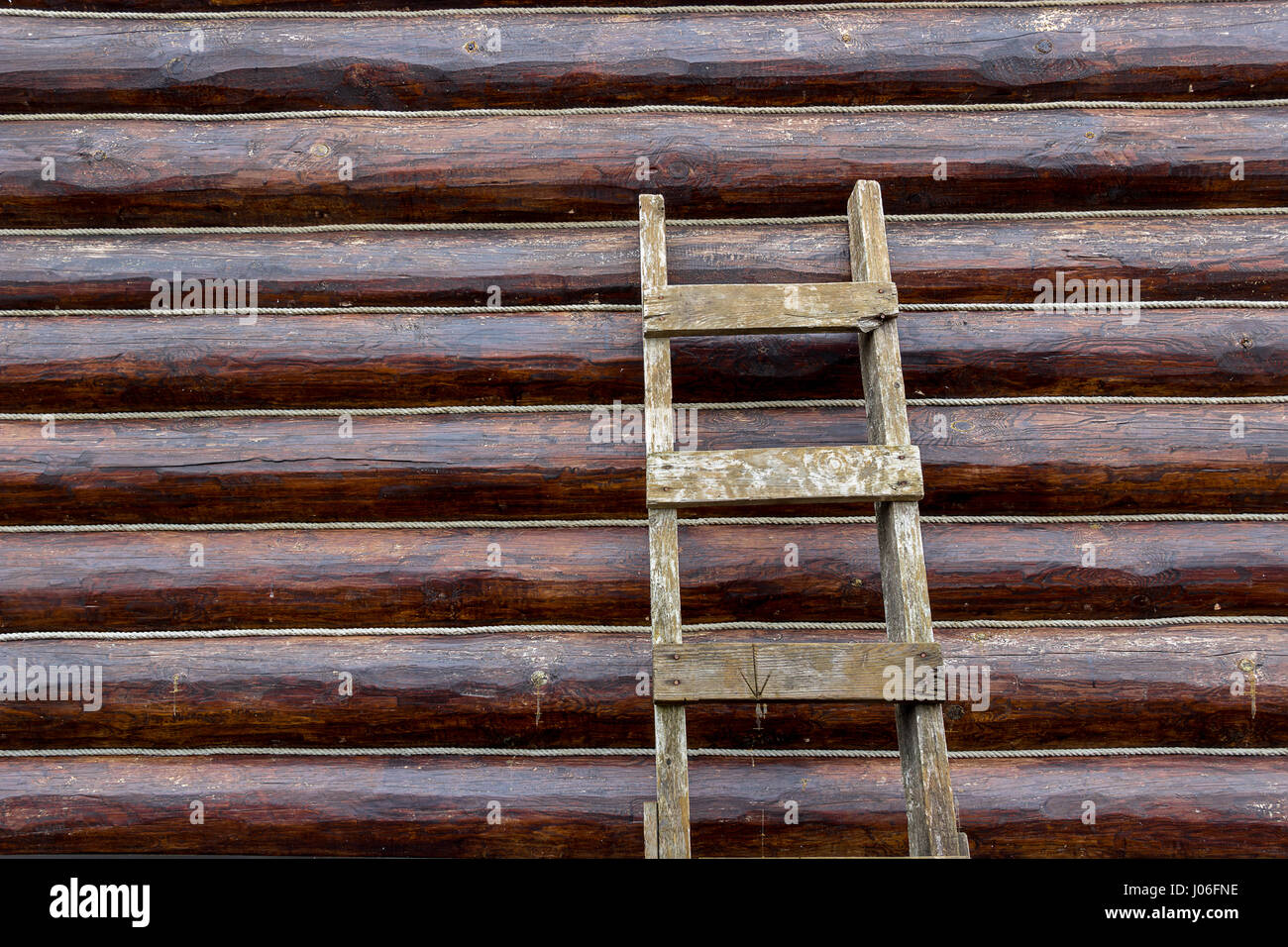 Neutral background wall of round logs of ropes and a lading textured staircase Stock Photo