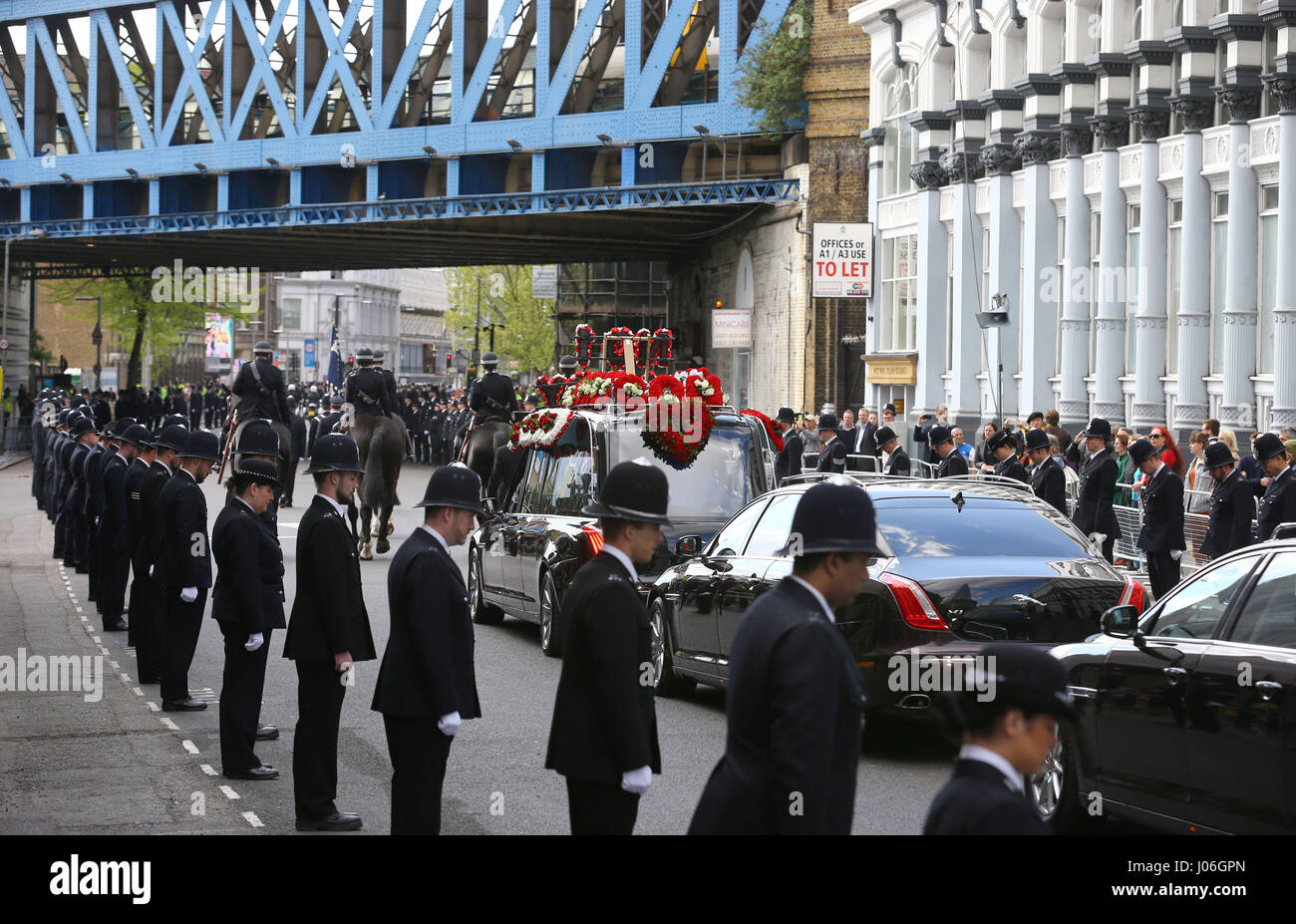 Police line the route as the coffin of Pc Keith Palmer leaves Southwark Cathedral in London after his funeral service. - Stock Image