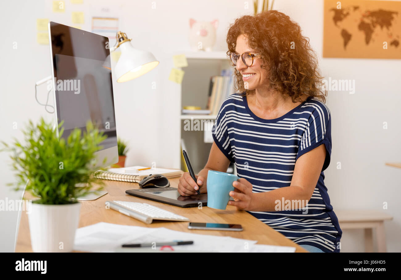 Middle age designer working on a desktop with a stylus pen - Stock Image