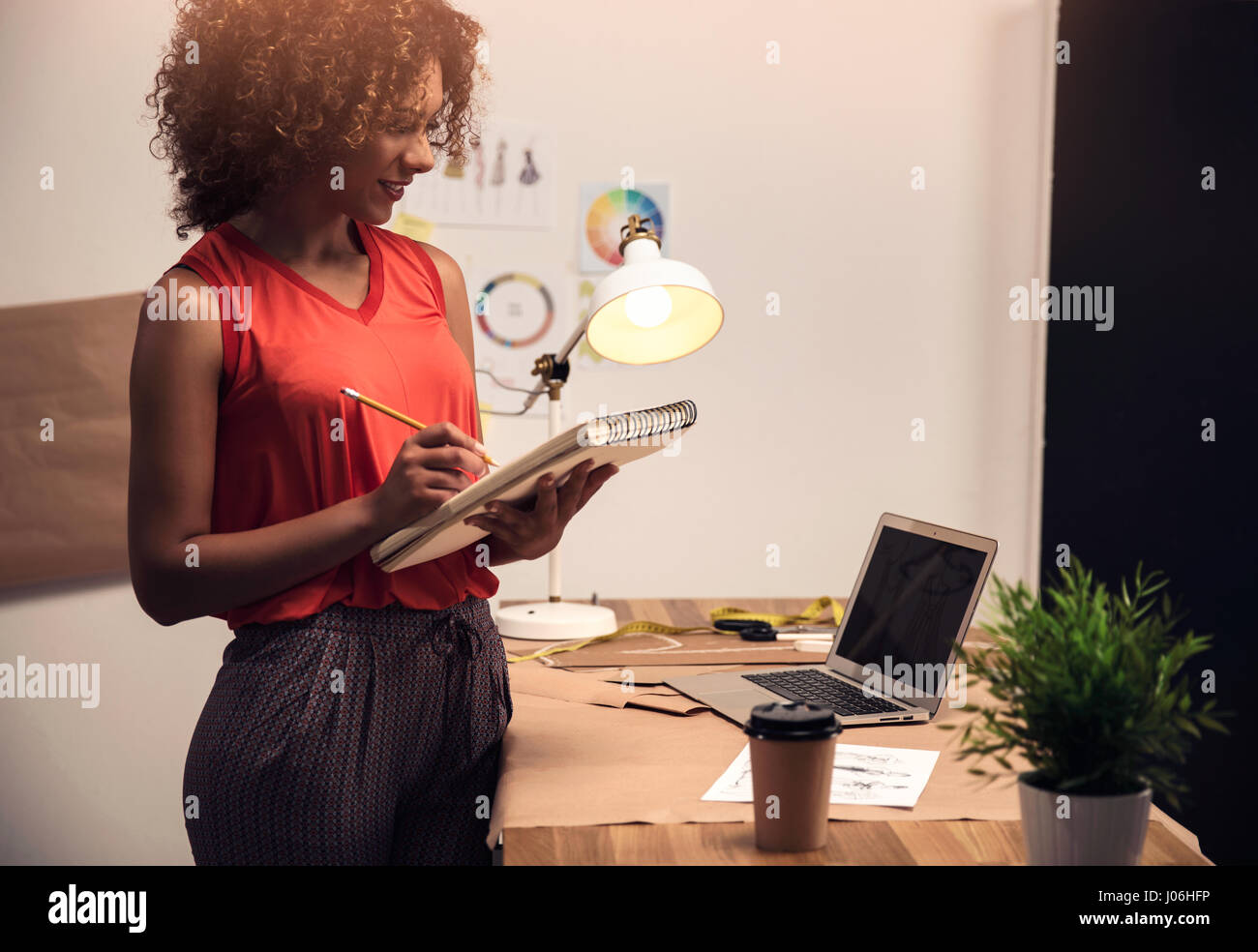 A young fashion designer working on her atelier - Stock Image