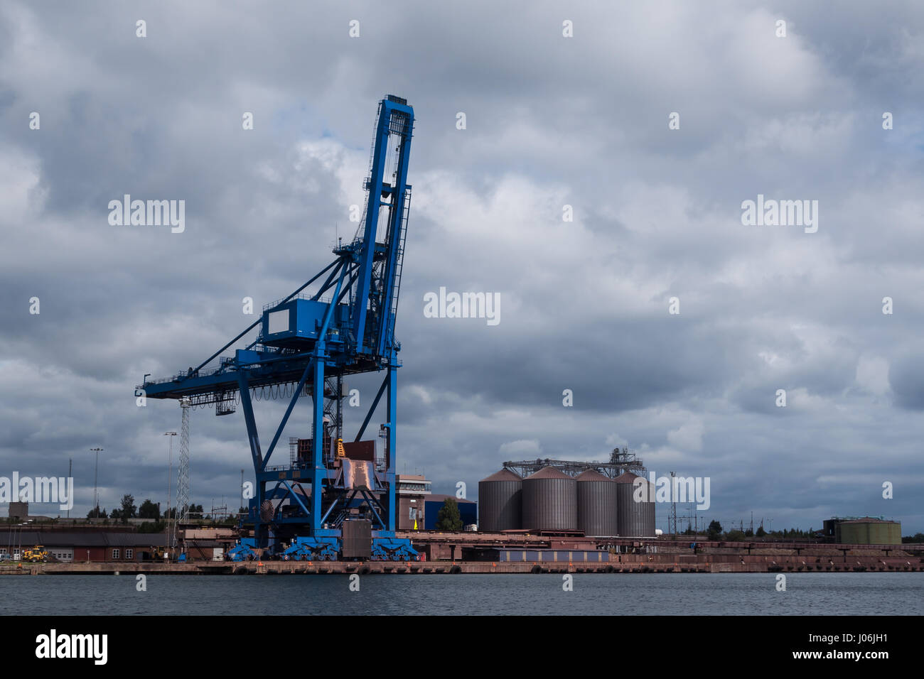 A crane and silos in an industrial harbour by the sea standing idle. - Stock Image