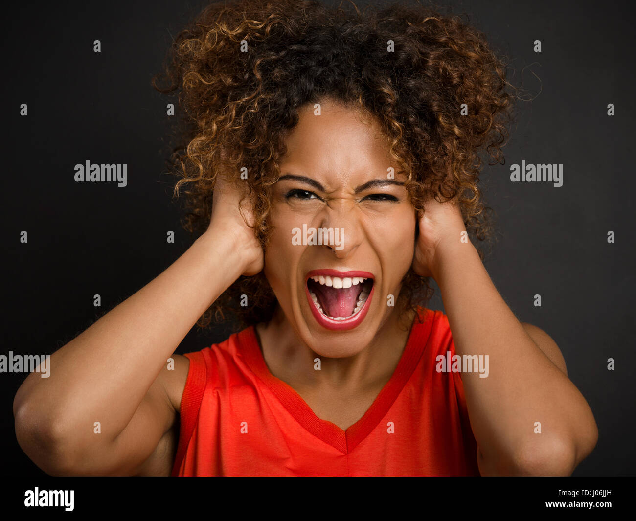 Portrait of an African American woman with hands on the head and yelling - Stock Image